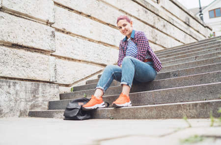 Portrait of smiling Beautiful modern young female teenager with extraordinary hairstyle color in checkered sitting on the old town stairs. Modern teens or young students concept image. Standard-Bild
