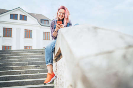Portrait of cheerfully smiling Beautiful modern young female teenager with extraordinary hairstyle color browsing the internet via a smartphone. Modern teens or cheerful students concept image.