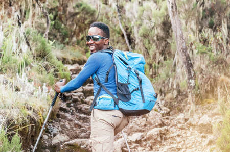 Portrait of a cheerfully smiling African-American Ethnicity young man in sunglasses. He having a walk with a backpack using trekking poles to Mweka gate, Kilimanjaro. Active climbing people concept.