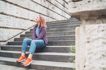 Smiling Beautiful modern young female teenager with extraordinary hairstyle color in checkered sitting on the old town stairs. Modern teens or young students concept image.