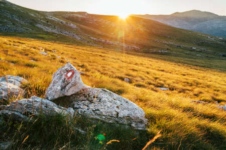 Rising Sun over the Sinjal or Dinara (1831 m) mountain - the highest point of Croatia in the Dinaric Alps on the border between Croatia and Bosnia and Herzegovina. Hiking trail mark painted on rock. Standard-Bild