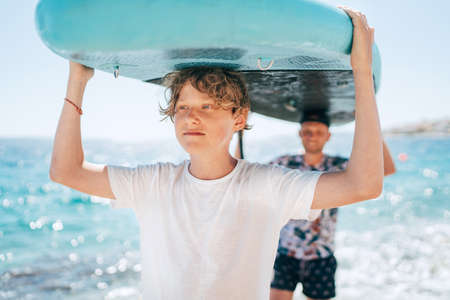 Blonde teenage son with father surfers smiling carrying the stand-up paddleboard with a paddle on the bright sunny day noon. Active family summer vacation time near the sea concept image.