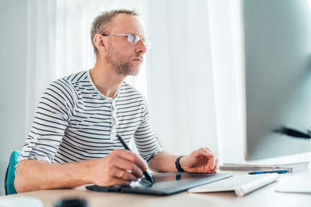 A middle-aged man in eyeglasses using a graphic tablet with pen and modern computer drawing artwork in his living room. Home office, distance or freelance work on worldwide quarantine time concept