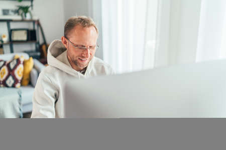 Smiling Middle-aged man in eyeglasses using a modern computer in his living room. Writing or Distance or freelance work on worldwide quarantine time concept