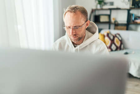 A middle-aged man in eyeglasses using a modern computer in his living room. Writing or Distance or freelance work on worldwide quarantine time concept Standard-Bild