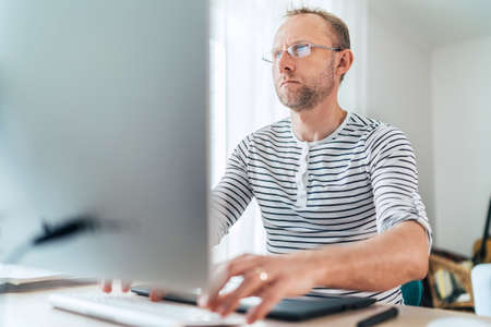 A middle-aged man in eyeglasses typing a text using a modern keyboard computer in his living room. Writing or Distance or freelance work on worldwide quarantine time concept