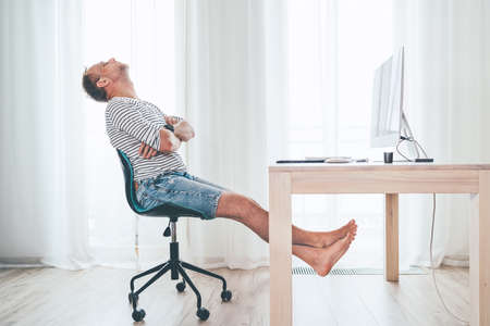 A middle-aged man relaxing on a swivel chair near the table with computer while he watching TV in living room. He stretching barefoot lags and resting. Streaming on worldwide quarantine time concept Standard-Bild
