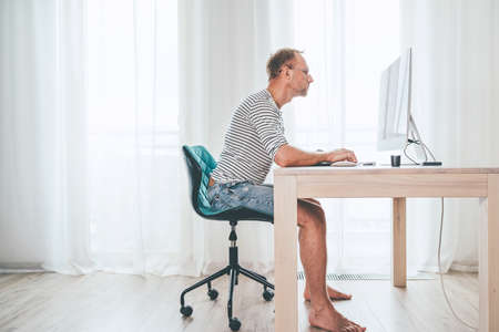 Barefoot Middle-aged writer man on a swivel chair typing down a text using the modern PC keyboard in the home living room. Novelist freelance on worldwide quarantine time concept