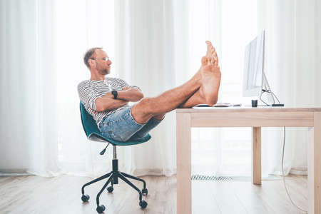 A middle-aged man in eyeglasses watching a modern computer in his living room. He put her barefoot lags on the table and relaxing. Video streaming on worldwide quarantine time concept Standard-Bild