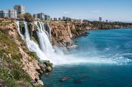 Lower Düden Falls drop off a rocky cliff falling from about 40 m into the Mediterranean Sea in amazing water clouds. Tourism and travel destination photo in Antalya, Turkey.