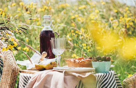 Served table still life view with tasty dessert fruit pie and vintage tableware, red wine and glasses in the green high meadow grass with a fresh spring flowers.