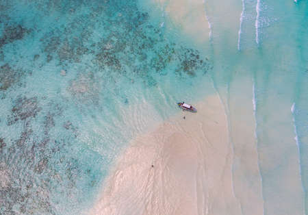 Aerial shot of the Mnemba Island white sand sandbanks washed with turquoise Indian ocean waves near the Zanzibar island, Tanzania. The couple came here on the motorboat, anchored it and having rest. 免版税图像
