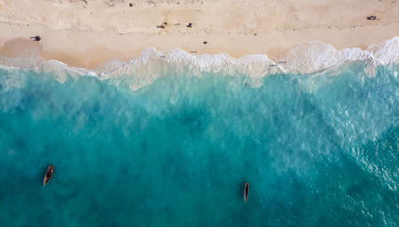Aerial shot of the white sand beach shore and emerald water with fishermen's boats floating on Indian ocean waves on the Zanzibar island, Tanzania.