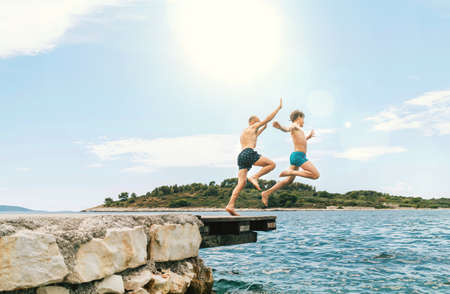Son with Father having a fun on a merry vacation days on Adriatic sea coast. They dressed swimming trunks jumping to the waives from the boat pier. Family time, fatherhood or childhood concept image.