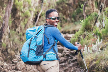 Portrait of a cheerfully smiling African-American Ethnicity young man in sunglasses. He having a walk with a backpack using trekking poles to Mweka gate, Kilimanjaro. Active climbing people concept