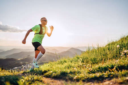Middle-aged mountain trail runner man dressed bright t-shirt with a backpack in sports sunglasses endurance running uphill by picturesque hills at sunset time. Sporty active people concept image. 免版税图像