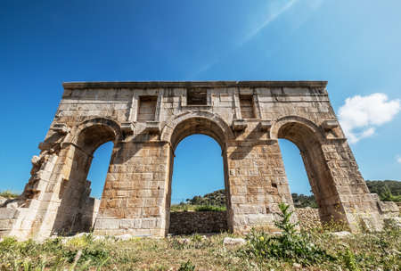 The symbol of ancient Patara (Lycia) city - Arch of Mettius Modestus, Mediterranean coast of Turkey. Architecture Art and traveling around the world concept image.