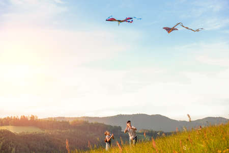 Smiling sister with a brother with launching colorful kites - popular outdoor toy on the high grass hills meadow. Happy childhood moments or outdoor time spending concept image.