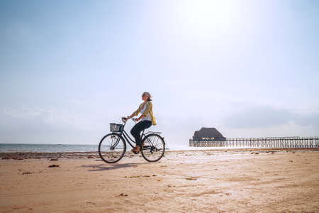 Young woman dressed light summer clothes riding old vintage bicycle with front basket on the lonely low tide ocean white sand coast on Kiwengwa beach on Zanzibar island, Tanzania.