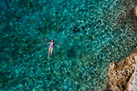 Young female floating on the back and relaxing on the warm turquoise Adriatic sea waves with rocky coastline. Carefree people vacation time concept aerial top view image. 免版税图像