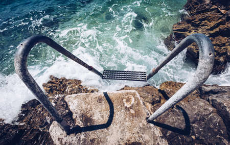 Wide angle shot of a metal ladder on the rocky shore beach washed by the foamy Adriatic sea waves.