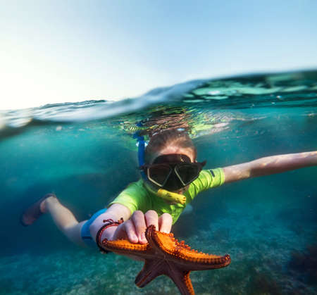 Underwater shot of a young teenage boy snorkeling with dive face mask in the blue Indian Ocean waves near the Zanzibar island with a big orange starfish in his hand. Exotic vacations concept image. 免版税图像