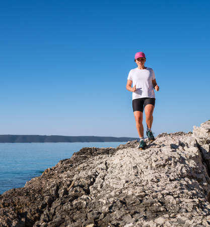 Young female dressed running sporty clothes and pink cap enjoying morning run race along the rocky calm sea coast. Sporty people trail running activities on vacation time concept image.
