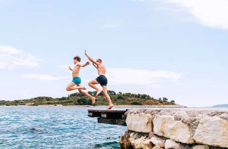 Son with Father having a fun on a merry vacation days on Adriatic sea coast. They dressed swimming trunks jumping to the waives from the boat pier. Family time, childhood or fatherhood concept image. 免版税图像