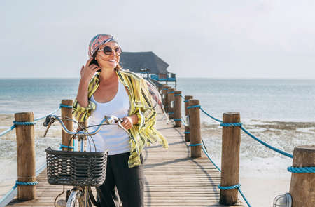Portrait of a smiling woman dressed in light summer clothes, sunglasses with bicycle on the wooden sea pier on the sandy Zanzibar beach.Careless vacation in the tropical countries concept image