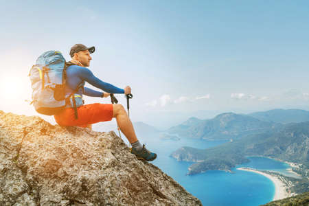 Young backpacker man sitting on cliff and enjoying the Mediterranean Sea bay at during Lycian Way trekking walk. Famous Likya Yolu Turkish route. Active sporty people vacations concept image
