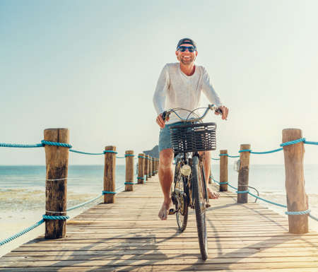 Portrait of a happy smiling man dressed in light summer clothes and sunglasses riding a bicycle on the wooden sea pier. Careless vacation in tropical countries concept image. 免版税图像