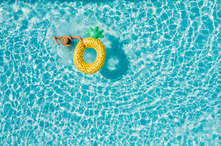 Top view of a young female in swimsuit bikini in a straw hat on blue swimming pool waves background with big inflatable Yellow Pineapple tube. Chill out a summer vacation in luxury resorts concept. 免版税图像
