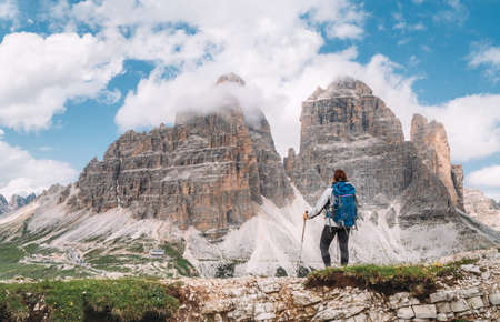 Female hiker walking with backpack and trekking poles on green mountain hill enjoying picturesque Tre Cime di Lavaredo formation 2999m in Dolomite Alps. Active people and mountain concept 免版税图像