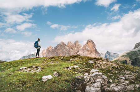 Woman trekker with backpack and trekking poles on green hill enjoying picturesque Dolomite Alps view near Tre Cime di Lavaredo formation in South Tyrol, Italy. Active people and mountain concept.