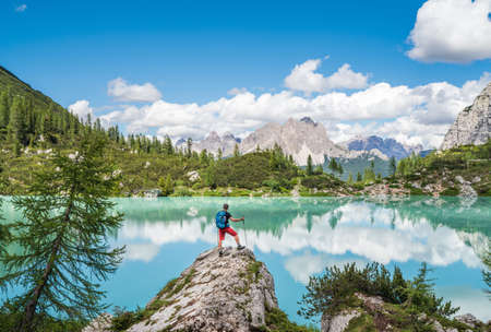 Backpacker with backpack enjoying the turquoise Lago di Sorapiss 1,925m altitude (mountain lake) view as he has mountain walk in Dolomite Mountains, Italy. Active people in nature concept. 免版税图像