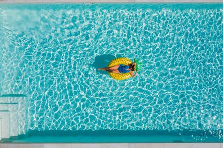 Sexy young female in swimsuit bikini, in a straw hat and sunglasses floating on blue swimming pool waves on giant inflatable Yellow Pineapple tube. Chill out summer vacation in luxury resorts concept.