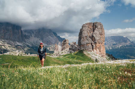 Smiling female trekker walking with backpack and trekking poles by green mountain hill with picturesque Dolomite Alps Cinque Torri formation on the background. Active people and mountains concept. 免版税图像