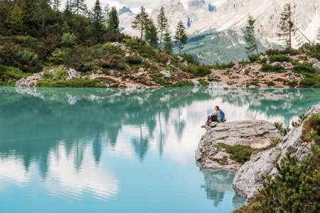 Backpacker woman with backpack enjoying the turquoise Lago di Sorapiss 1,925m altitude (mountain lake) view as he has mountain walk in Dolomite Mountains, Italy. Active people in nature concept.