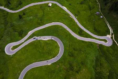 Passo Gardena Green hills Aerial drone shot of curved mountainous road with cars passing through curves. Transportation, safety driving, traveling, car rental concept. 免版税图像