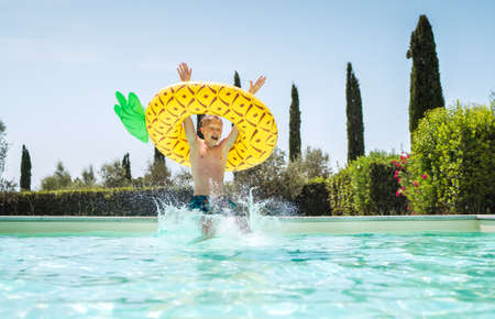 Cheerful Screaming boy in yellow pineapple inflatable ring having fun and jumping into swimming pool. Merry childhood or summer holidays concept image. 免版税图像