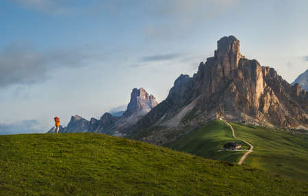 A photographer using a camera making a Beautiful early morning Dolomites Alps mountain landscape photo. Giau Pass or Passo di Giau - 2236m mountain pass in the province of Belluno in Italy.