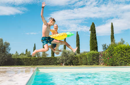 Laughing Son with Father in the inflatable ring having fun on a merry vacation. Cheerful fooling around they jumping to the swimming pool. Family time, fatherhood, or childhood concept image. 免版税图像