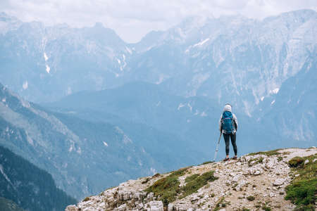 Woman trekker with backpack and trekking poles on the hill enjoying picturesque Dolomite Alps view near Tre Cime di Lavaredo formation in South Tyrol, Italy. Active people and mountain concept.