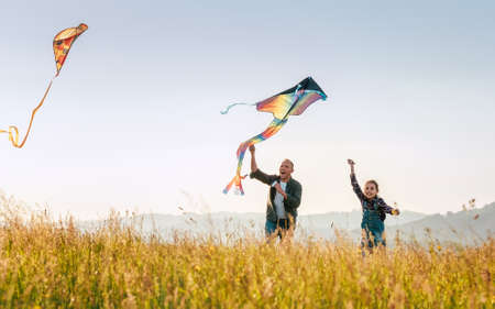 Outdoor photo of a father with daughter as they releasing colorful kites on the high grass meadow sincerely laughing. Warm family moments or outdoor time spending concept image. 免版税图像