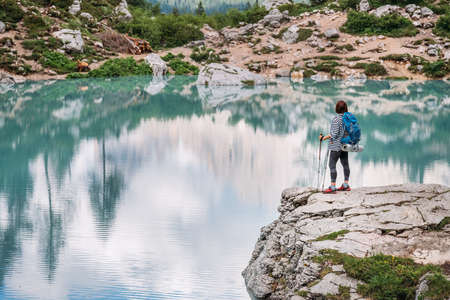 Backpacker woman with backpack and trekking poles enjoying the turquoise Lago di Sorapiss 1925m altitude lake view during mountain walking in Dolomite Mountains, Italy. Active people in nature concept 免版税图像