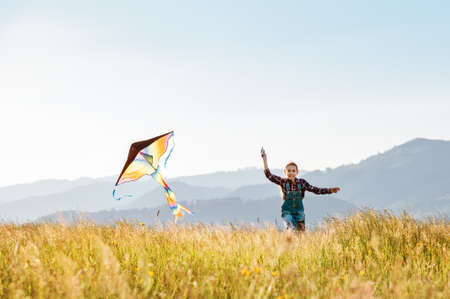 Smiling girl with flying colorful kite running on the high grass meadow in the mountain fields. 9YO Happy childhood moments or outdoor time spending concept image. 免版税图像