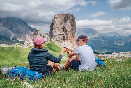 Mother and son backpackers have a picnic on a green mountain hill with the picturesque Dolomite Alps Cinque Torri formation, Nothern Italy. Family values, active people and mountains concept.