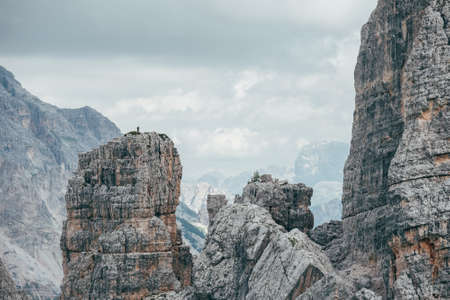 Small climber silhouette standing on impressive and picturesque Cinque Torri formation cliff who enjoying Dolomite Alps panorama. Extreme Active people and mountains concept.