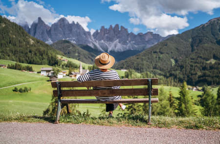 Young fashionable dressed female in straw hat sitting on a bench enjoying Santa Maddalena village view and stunning picturesque Dolomite Alps peaks in Val di Funes valley, South Tyrol, Italy. 免版税图像