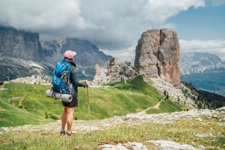 Female trekker walking with backpack and trekking poles by green mountain hill and enjoying the picturesque Dolomite Alps Cinque Torri formation. Active people and mountains concept. 免版税图像